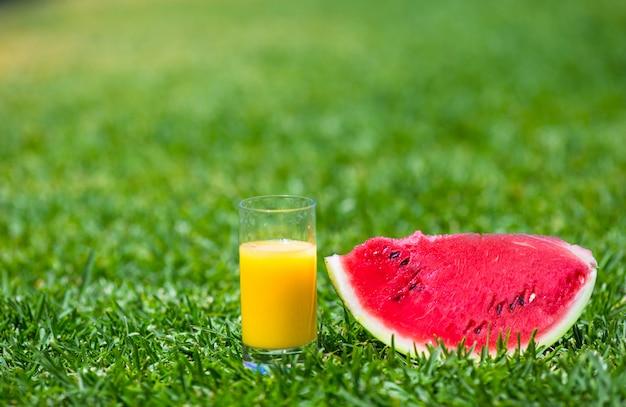 Thème été et frais: pastèque en tranche mûre rouge et verre de jus d'orange sur de l'herbe verte Photo Premium