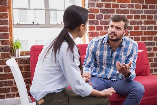 Thérapeute à l'écoute de son patient sur le canapé au bureau Photo Premium