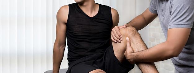 Thérapeute soignant le genou blessé d'un patient sportif en clinique Photo Premium