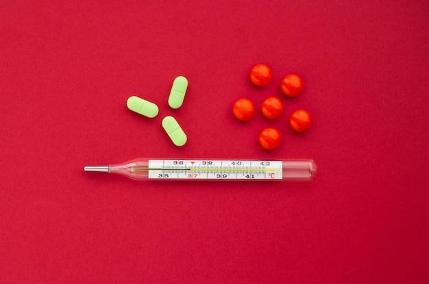 Thermomètre à mercure avec des comprimés orange et verts sur fond rouge, concept de santé Photo Premium