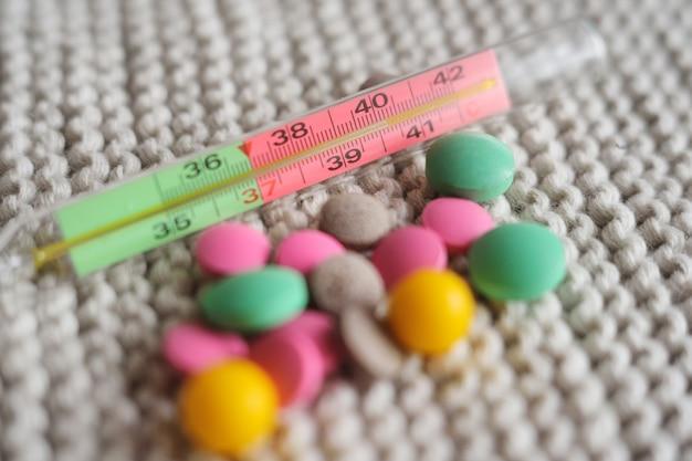 Thermomètre et nombreux comprimés colorés en gros plan sur un fond tricoté Photo Premium