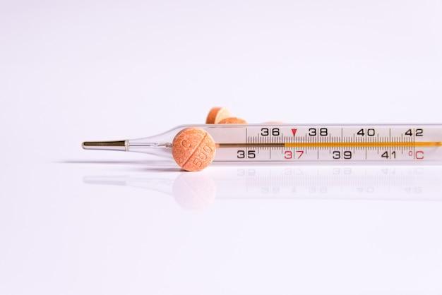 Un thermomètre et des vitamines sur un fond blanc. Photo Premium