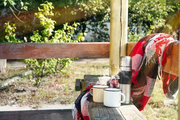 Thermos avec thé chaud sur une table en bois. Photo Premium