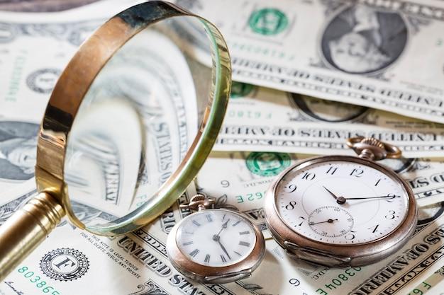 Time Is Money Finance Concept Avec Vieilles Horloges Vintage, Billets D'un Dollar Et Loupe Photo Premium