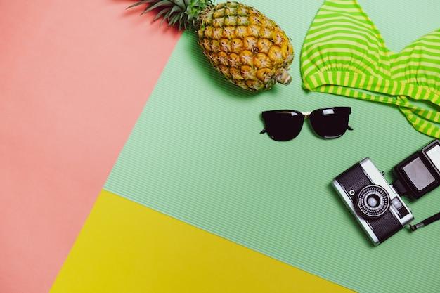 Time to relax: aller à la plage et voyager avec des lunettes de soleil, un appareil photo, un bikini et des fruits à l'ananas sur fond pastel Photo Premium