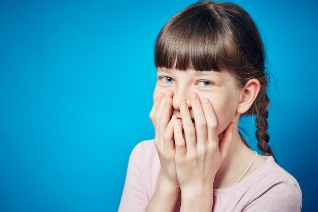 Timide fille embarrassée souriante couvrant la bouche avec les mains. portrait affectif jeune enfant mignon Photo Premium