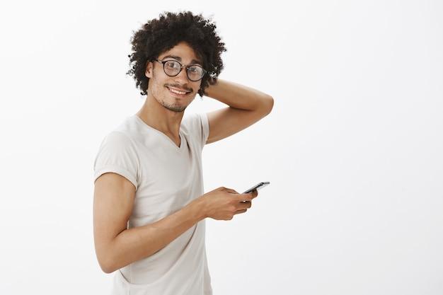 Timide Homme Mignon Dans Des Verres à L'aide De Téléphone Portable Et Souriant Maladroit Photo gratuit