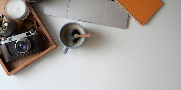 Tir aérien d'un espace de travail confortable avec un ordinateur portable, une caméra, une tasse à café et des fournitures de bureau sur un bureau blanc Photo Premium