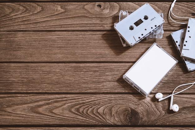 Tir aérien de la vieille cassette audio rétro avec écouteur sur fond en bois rétro vintage, vue de dessus plat lay avec espace copie. Photo Premium