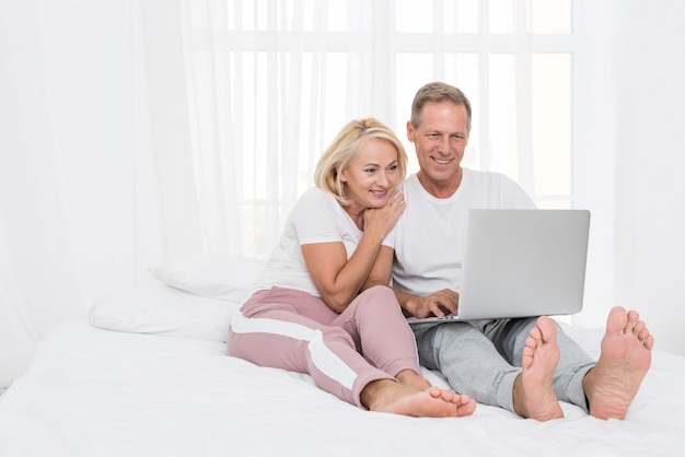 Tir Complet Couple Heureux Avec Un Ordinateur Portable Dans La Chambre Photo gratuit