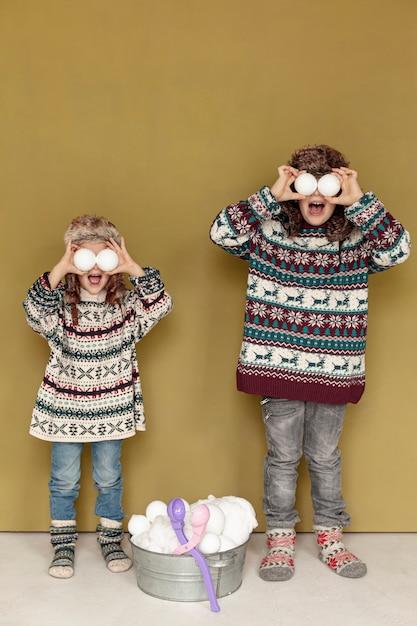 Tir complet enfants jouant avec des boules de neige à l'intérieur Photo gratuit