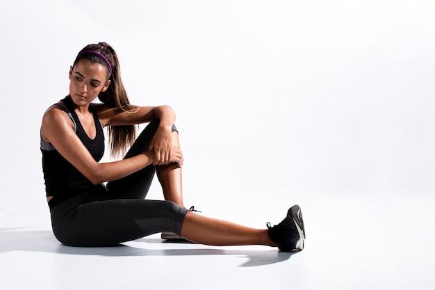 Tir complet femme en costume de gym assis Photo gratuit