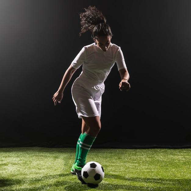 Tir complet femme jouant au football Photo gratuit
