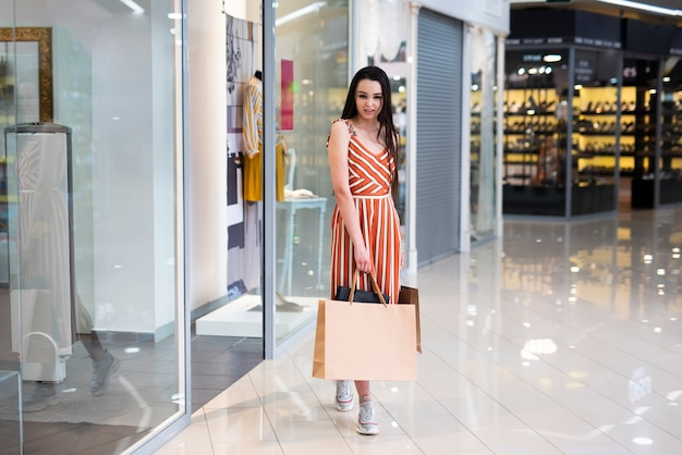 Tir complet femme posant à l'extérieur du magasin Photo gratuit