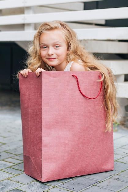 Tir Complet Fille Assise Dans Un Sac Cadeau Photo gratuit