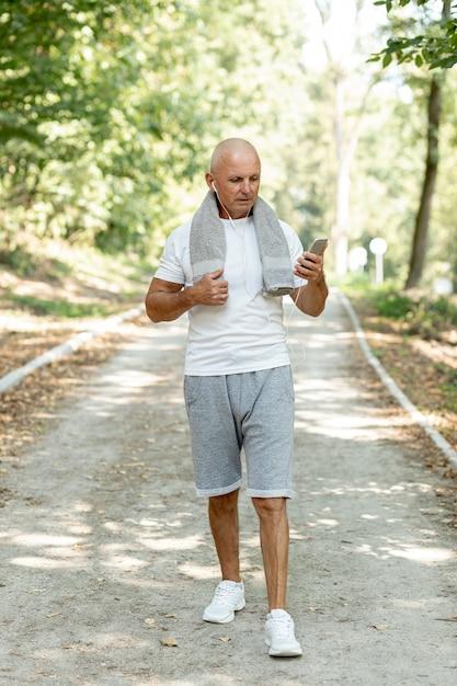 Tir complet homme aîné marchant dans la forêt Photo gratuit