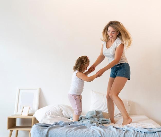 Tir Complet Mère Et Fille Danser Dans Son Lit Photo gratuit