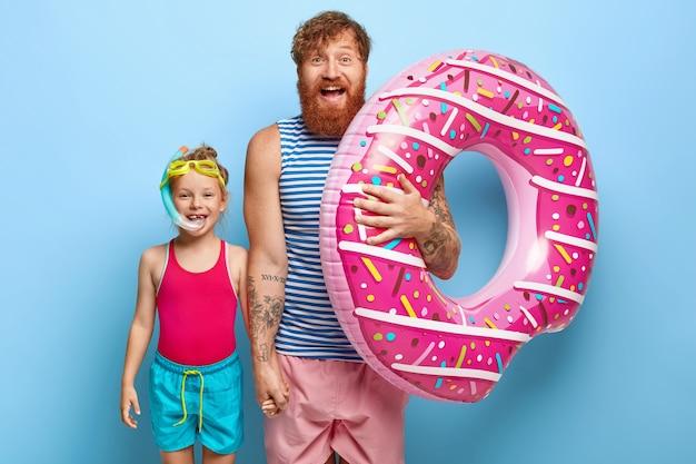 Tir De L'heureux Père Et Fille De Gingembre Posant Dans Des Tenues De Piscine Photo gratuit