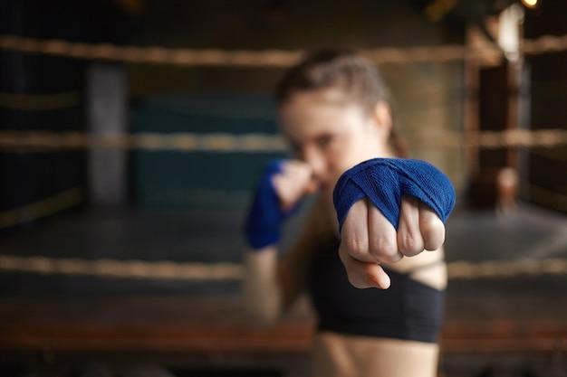 Tir Horizontal De L'élégante Jeune Femme Boxer Portant Des Bandages Bleus à L'intérieur De La Formation, Se Préparer Pour Un Match De Boxe, Tendre La Main Photo gratuit