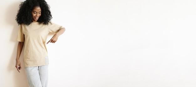 Tir à L'intérieur De La Belle Jeune Femme à La Peau Sombre Avec Un Joli Sourire Et Une Coiffure Afro Regardant Son T-shirt Oversize Décontracté Et Pointant Le Doigt Dessus Photo gratuit