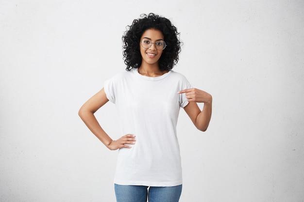 Tir Intérieur De Jeune Femme Métisse Sympathique Positive Dans Des Verres Pointant Photo gratuit