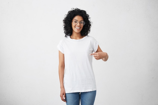 Tir Intérieur De Joyeuse Jeune Femme Afro-américaine Souriante Aux Cheveux Bouclés Pointant L'index Photo gratuit