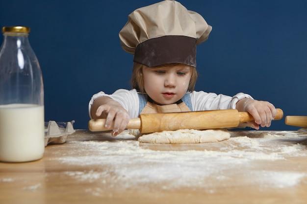 Tir Isolé De La Belle Petite Fille D'apparence Européenne Tenant Un Rouleau à Pâtisserie Tout En Faisant Des Biscuits Ou D'autres Pâtisseries à L'atelier Culinaire Photo gratuit