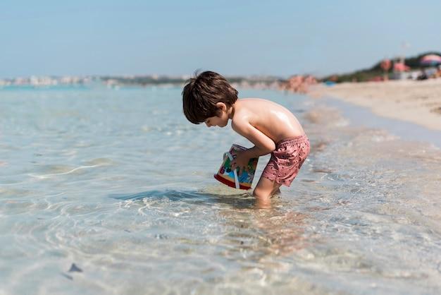 Tir latéral d'un enfant jouant dans l'eau Photo gratuit