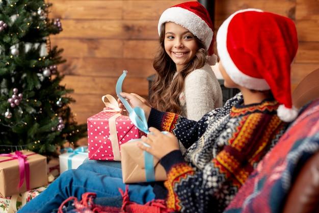 Tir Moyen Enfants Heureux Avec Des Cadeaux Près De L'arbre De Noël Photo gratuit