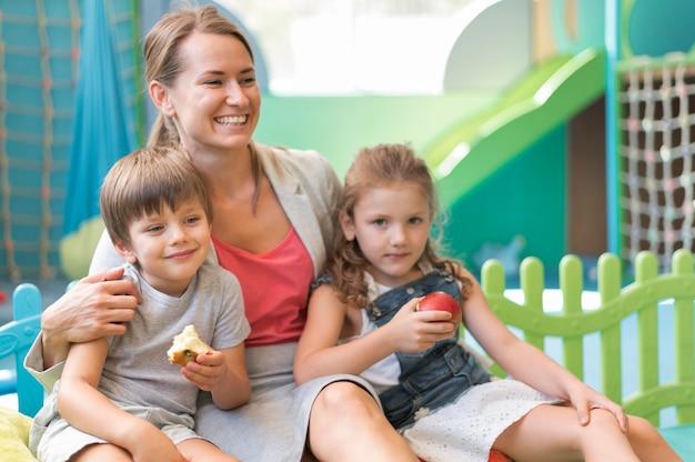 Tir Moyen Heureux Enseignant Tenant Des Enfants Photo gratuit