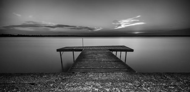 Tir En Niveaux De Gris D'un Chemin En Bois Sur La Mer Sous Un Ciel Clair Photo gratuit