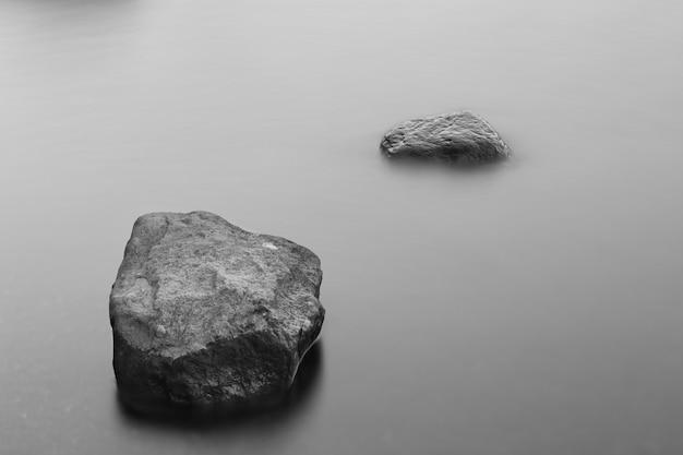 Tir En Niveaux De Gris De Formations Rocheuses Dans L'océan Gelé Couvert De Brouillard Photo gratuit