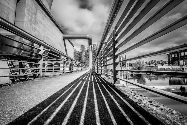 Tir En Niveaux De Gris D'un Pont Sous Un Ciel Nuageux Photo gratuit