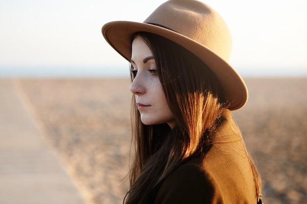 Tir En Plein Air De La Belle Jeune Femme Européenne Aux Longs Cheveux Noirs Portant Un Chapeau Tout En Marchant Sur La Plage De La Ville, Se Sentant Triste Et Solitaire Photo gratuit