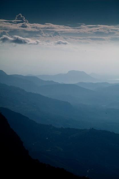 Tir Vertical De La Belle Chaîne De Montagnes Et Du Ciel Nuageux Tôt Le Matin Photo gratuit
