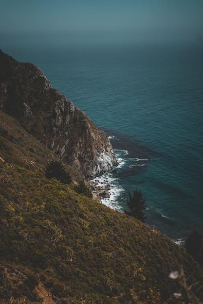 Tir Vertical D'une Côte Verte Vallonnée Et D'un Océan Bleu Avec Des Rochers Photo gratuit