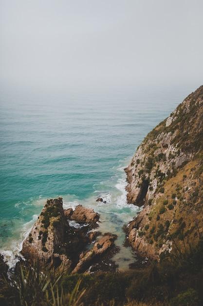 Tir Vertical De Gros Rochers à Nugget Point Ahuriri, Nouvelle-zélande Avec Un Fond Brumeux Photo gratuit