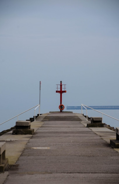 Tir Vertical D'une Jetée Menant à L'océan Sous Le Ciel Clair Photo gratuit
