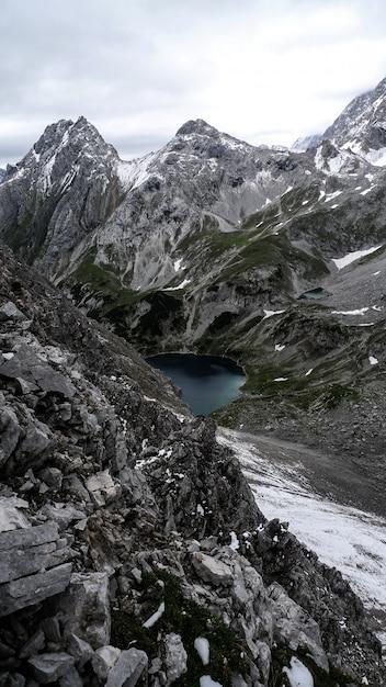 Tir Vertical D'un Lac Entouré De Montagnes Sous Un Ciel Nuageux Photo gratuit