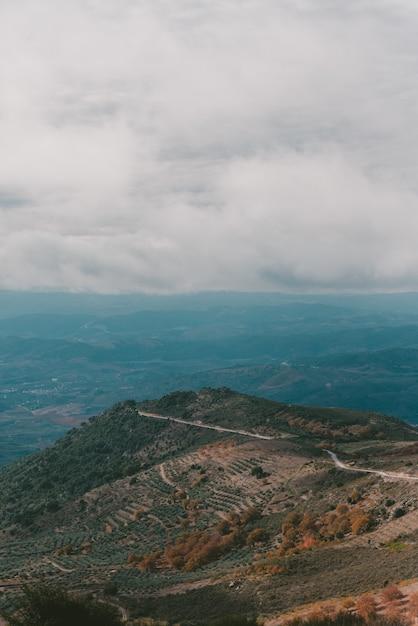 Tir Vertical D'une Montagne Sous Un Ciel Nuageux Photo gratuit