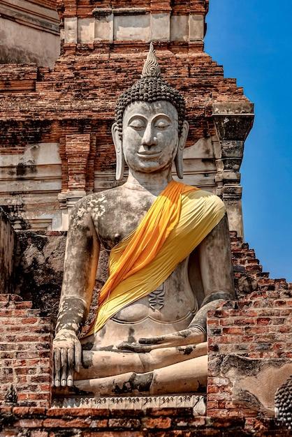 Tir Vertical D'une Vieille Statue De Bouddha Recouverte De Tissu Jaune Et Orange Photo gratuit