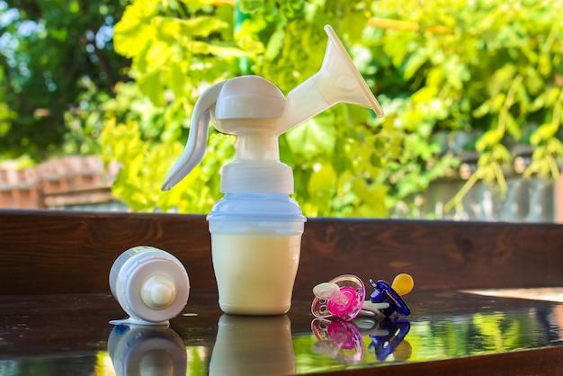 Tire-lait, bouteille de lait et sucettes sur la table Photo Premium