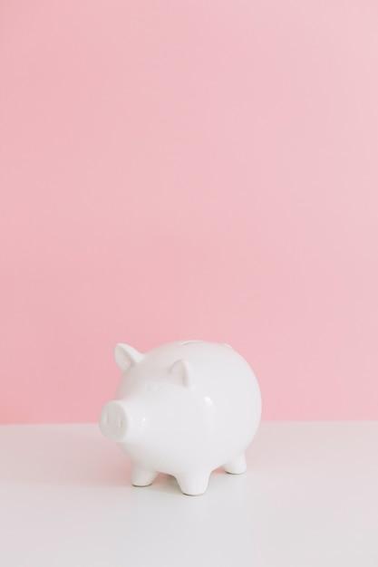 Tirelire blanche sur un bureau blanc sur fond rose Photo gratuit