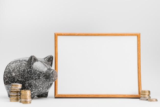Tirelire en céramique avec pile de pièces près du tableau blanc sur fond blanc Photo gratuit