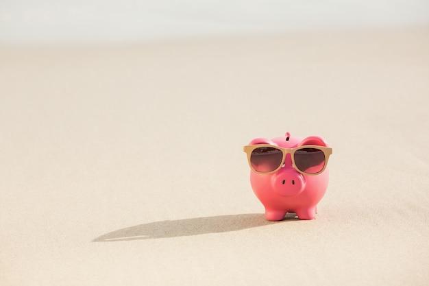 Tirelire d'été avec des lunettes de soleil sur le sable Photo gratuit