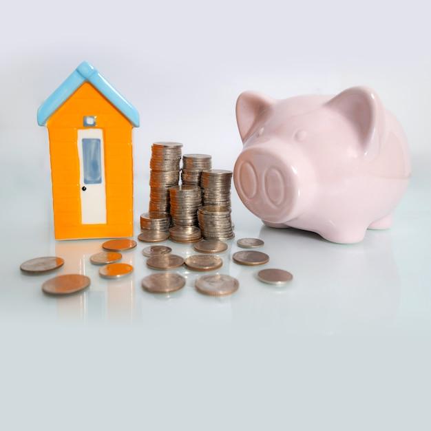 Tirelire avec petite maison et pièce de monnaie sur fond blanc Photo Premium
