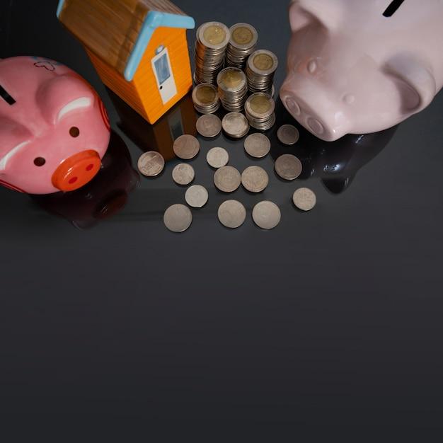 Tirelire avec petite maison et pièce de monnaie sur fond noir Photo Premium