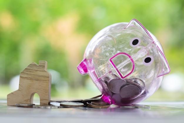 Tirelire et pièces d'argent près de la maison miniature. Photo Premium