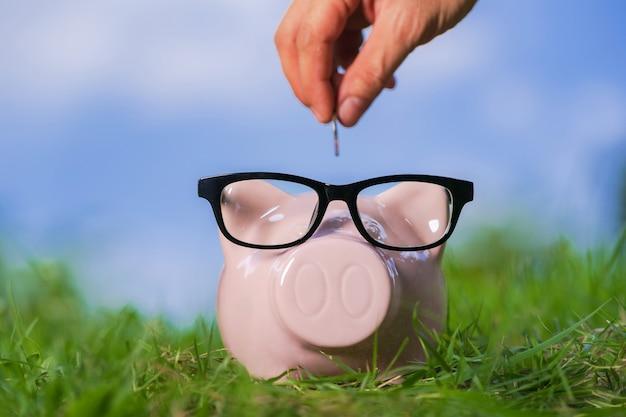 Tirelire rose avec des lunettes sur l'herbe et la main mettant une pièce de monnaie Photo Premium