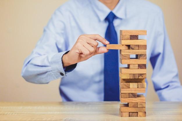 Tirer à la main ou placer des blocs de bois sur la tour, plan et stratégie en affaires Photo Premium